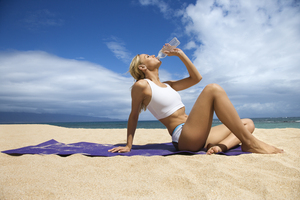 Woman on the beach drinking water