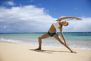 Woman on Beach Stretching with Yoga